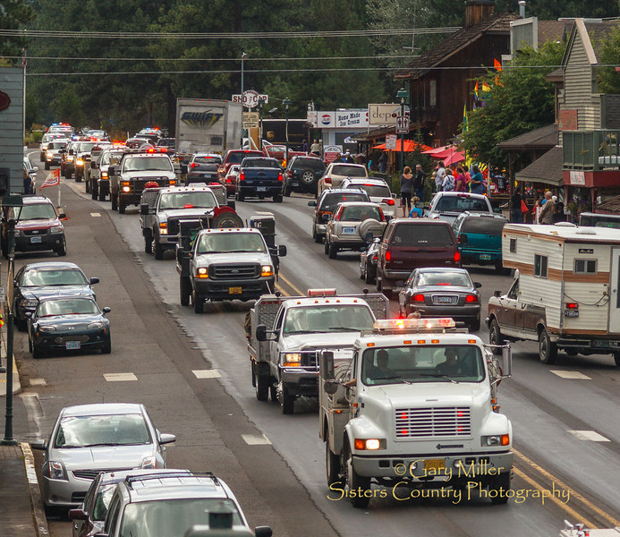 Firefighters honor a fallen comrade, faller and firefighter John Hammack, in a procession of over 40 vehicles that wound its's way down Cascade Avenue in Sisters, Oregon en route from the fire where he was killed on the lines delivering his body to a funeral chapel in nearby Redmond. Hammack was killed when the top of a tree he was cutting on a fireline broke off and fell killing him and seriously injuring his cutting partner Norm (Jay) Crawford. Copyright © 2013 Gary N. Miller, Sisters Country Photography