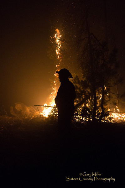D9 Dozer Operator Matt Cyrus inspectes encroaching fire during night operations on a fire line bordering the Sisters Wilderness. Images taken while working with a dozer crew on the Pole Creek Fire  on September 11, 2012 - Sisters, Oregon - Gary N. Miller - Sisters Country Photography