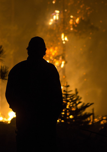 Dozer Operator Scott Glidewall ponders the oncoming fire during night operations on a fire line bordering the Sisters Wilderness. Images taken while working with a dozer crew on the Pole Creek Fire  on September 11, 2012 - Sisters, Oregon - Gary N. Miller - Sisters Country Photography