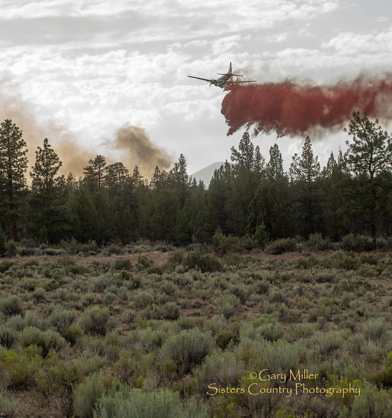Tanker 42 circles in over residences for a retardant drop as air tankers and multi-agency fire crews fought Fire Incident 395 off of Mustang Rd. which threatened homes in Squaw Creek Canyon Estates after a lightning strike from a major storm cell that came over the Oregon Cascades on July 31, 2013. Copyright © 2013 Gary N. Miller, Sisters Country Photography