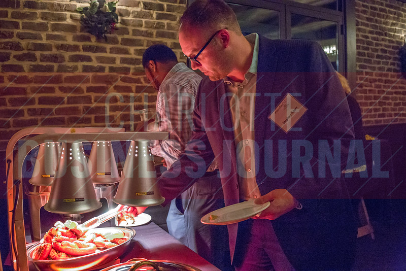 Attendees of the NextGenCLT:Pivot event held at Olde Mecklenburg Brewery network, connect and enjoy food.