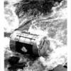 The empty 750-pound barrel in which John David Munday had ridden over Niagar aFalls lies in shallow waternear the falls Oct. 5 1985. Munday got safely out of the barrel some time before it was retrieved. He'd already attempted the stunt the previous July, but had been stopped before he could complete his ride over the falls. Rob McElroy photo for AP.
