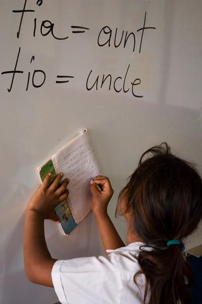 Girl copies English lesson from board in school, Las Camelias, Nicaragua.
