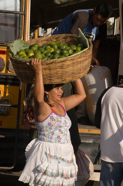 Woman carrying basket of tangerines on head, Granada, Nicaragua