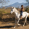 Boy rides horse bareback with Volcán Mombacho in background, La Prusia, Nicaragua.