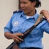 Smiling policewoman adjusts gun, San Carlos, Nicaragua.