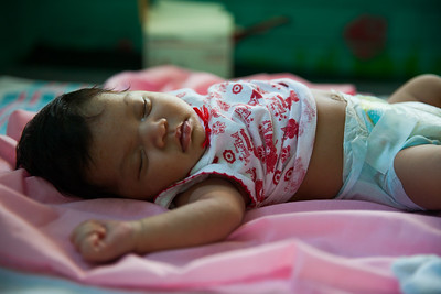 An infant, sleeping on the exam table, was brought in by his mother running a high fever.