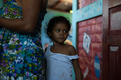 A young girl, hiding behind her mother is nervously waiting to see Dr. Gutierrez.
