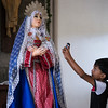 Boy takes photo of statue of Mary