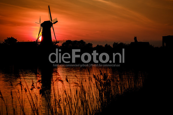 Sunset on a Dutch windmill by the river