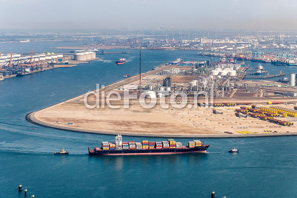 Containership pulled by tugboats enters the Port of Rotterdam