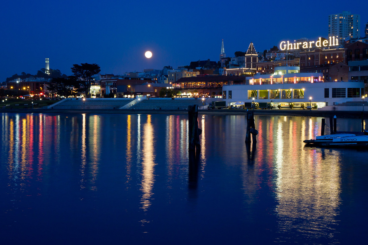 Reflections of Coit Tower, the moon, Ghirardelli Square, Aquatic Park, and the Maritime Museum at twilight.