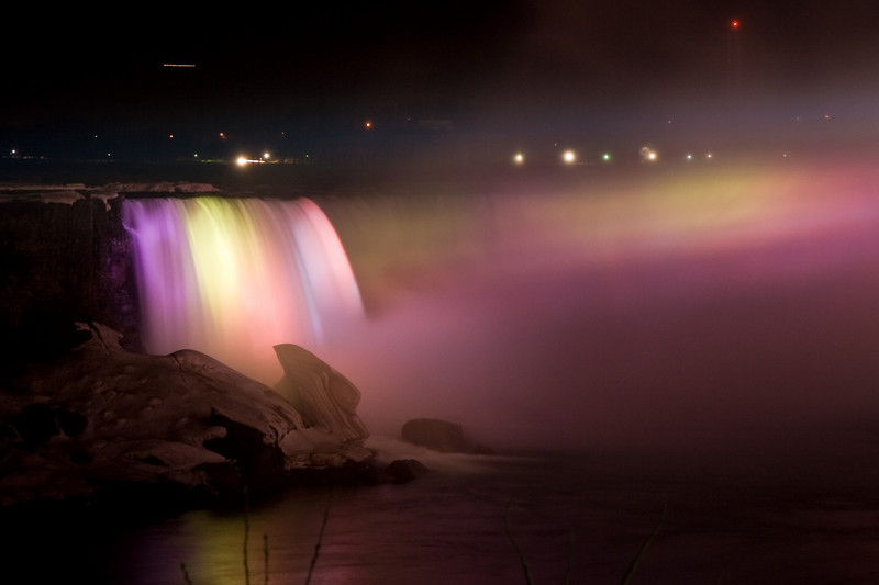 A part of Horseshoe Falls at night lit with colored spotlights.
