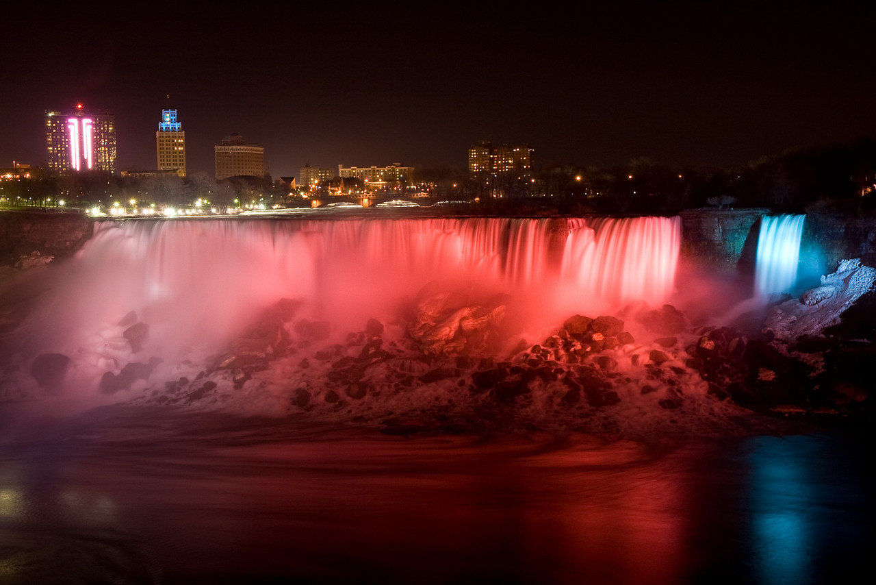 American Niagara Falls at night lit from the Canadian side with Niagara Falls, New York buildings in the background.