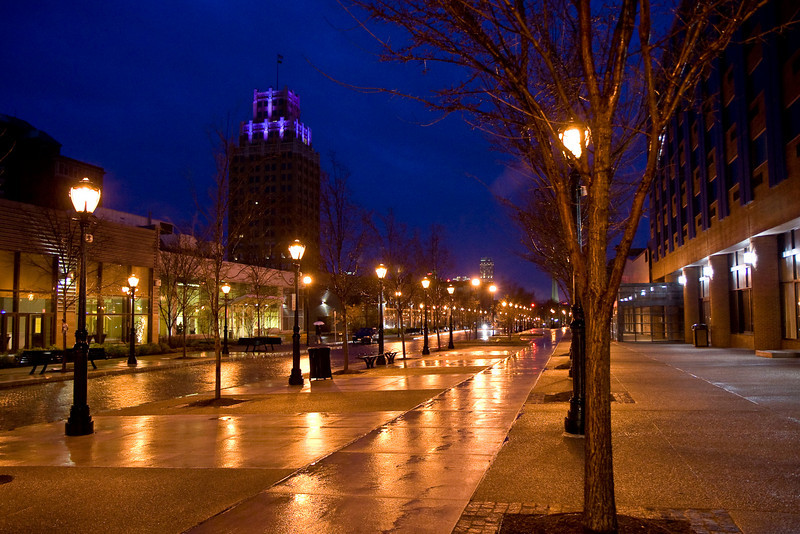 Night scene of the street after a rain. Hotel on the right and conference center on the left.