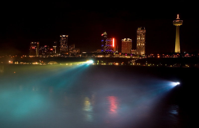 Niagara Falls, Canada at night with powerful colored lights directed at falls.