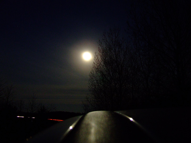Moon peeking through the trees, taken on a clear crisp night in Auldearn. The car lights are on the A96