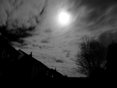Evening sky. Moon behind passing cloud.
