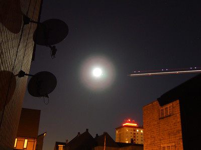 A full moon. Light trails from a passing aircraft.