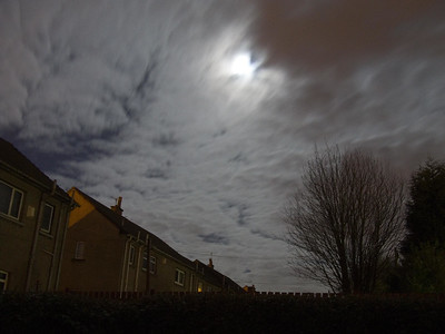 Evening sky. Moon behind passing cloud