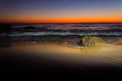Lit rock on the beach at Crystal Cove