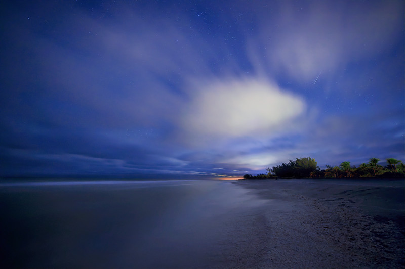Stars and meteors breaking through the clouds above Turner Beach in the Gulf of Mexico on Captiva Island, Florida.