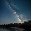 Meteors and the Milky Way over pine trees along the shore of Lake Michigan in Wilderness State Park near Mackinaw, Northern Michigan