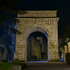 The white marble Arch of Augustus built in the First Century BC lit up at night in the city of Susa, Piedmont, Italy.  It was built to commemorate the renewed alliance between Emperor Augustus and Marcus Julius Cottius, a Celto-Ligurian ruler who had been made King and Roman prefect of the Cottian Alps.