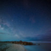 The Milky Way and meteors breaking through the clouds above Turner Beach in the Gulf of Mexico on Captiva, Florida
