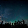 Northern lights, airglow and clouds with stars over the forest at Wilderness State Park near Mackinaw City, Michigan