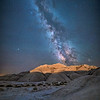 The lights from the train that runs through the Oglala National Grassland light up the badlands of Toadstool Geological Park with the Milky Way overhead and a solitary evening primrose wildflower in the foreground, Northwestern Nebraska