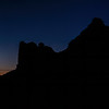 The Waning Crescent moon rising behind the Courthouse Towers section of Arches National Park near Moab, Utah