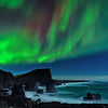 Northern lights over the sea stacks, waves and rocky shoreline of the Greenland Sea on the Reykjanes Peninsula, Iceland