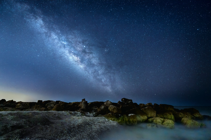 The Milky Way and Jupiter over the rocks at Turner Beach on Captiva Island, Florida