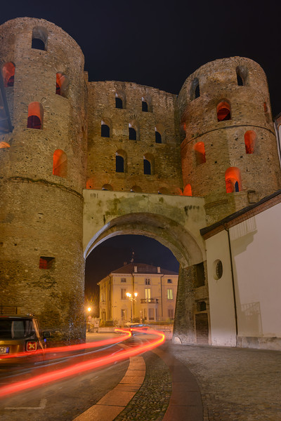 Car lights at night going through the Savoy Gate (Gate of Paradise) Susa, Piedmont, Italy
