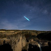 A shooting star appears over Palouse Falls on a moonlit night, Southeast Washington, Washington State. Shadow of the photographer appears in the lower left hand corner.