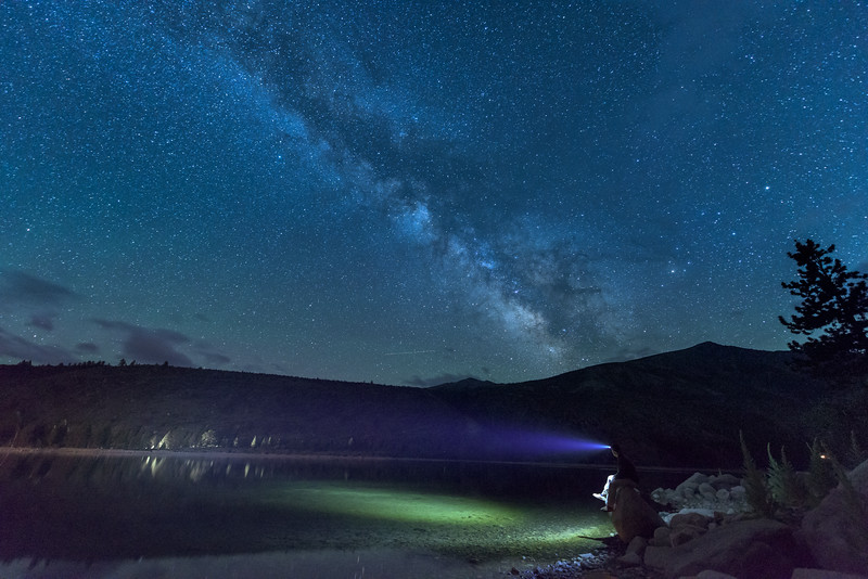 The Milky Way over Twin Lakes near Bridgeport, California with headlamp shining on the lake