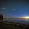 An incredible fireball meteor streaks across the sky over Lake Michigan near the Mackinaw Bridge.