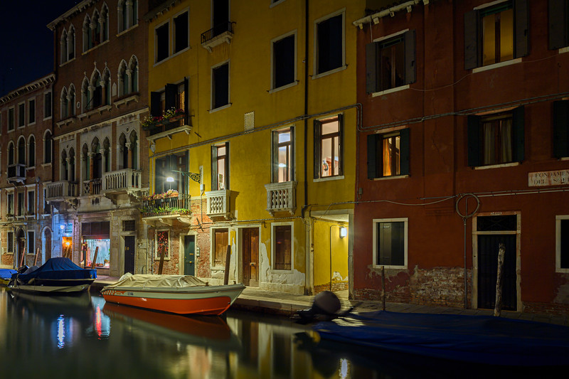 Covered boats along a canal at night in Venice, Italy
