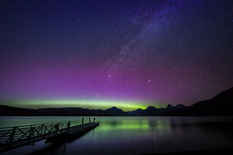 Lone figure at the end of the dock views the Northern Lights and Milky Way over Lake McDonald, Glacier National Park, Montana