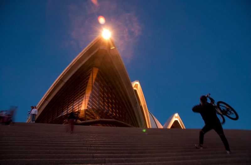 Cyclist Running Up Steps Of Sydney Opera House