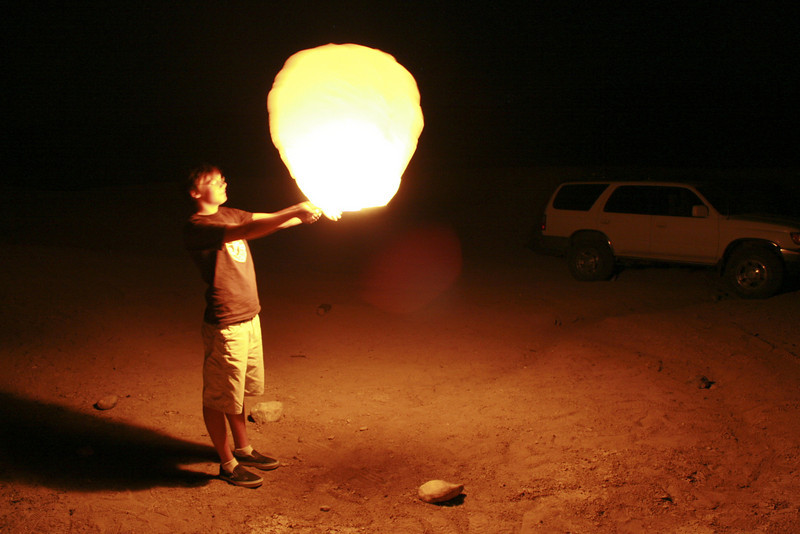 He is holding a fire ballon.  Basically it is a small hot arm ballon.