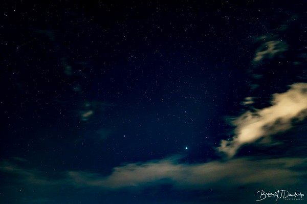 The night sky viewed through a gap in the coulds.