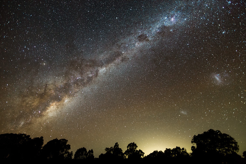 Milky Way and Magellenic Clouds over the distant lights of Melbourne, from Heathcote, Victoria.