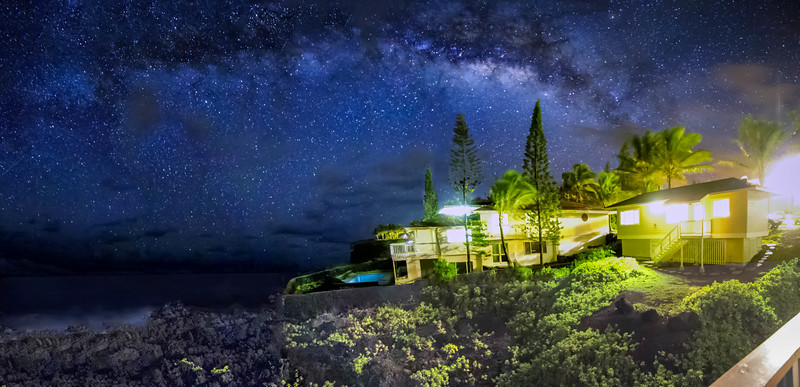 Milky way over houses and shore in Hawaii
