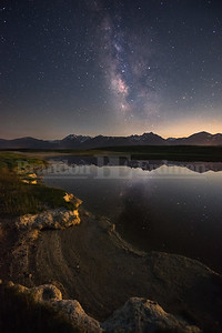 The milky way and mountains reflect off of a hot spring fed pond in California's Eastern Sierra