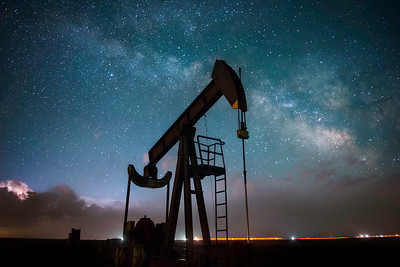 An oil pumpjack beneath the Milky Way and a distant lightning storm.