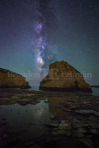 Milky way and star reflections in a tide pool at Shark Fin Cove in Davenport, California
