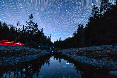I like shooting star trails when there is still some color in the sky. This is 136 frames stacked from 8:17 – 10:02 PM on May 20, 2015 of Hunter's Brook on Hunter's Beach in Acadia National Park, Maine, facing north for circular star trails around Polaris. I started shortly before the beginning of nautical twilight when stars were just becoming visible and the sky was still blue, and shot until the end of astronomic twilight, about an hour and forty-five minutes. After dark we went back to the truck to grab cold pizza and some warm blankets to enjoy the view while the cameras were clicking away, leaving some light trails with our headlamps and flashlights.   I ramped the exposure from ISO 1250 to 2500 with DslrDashboard on a Nexus 7 tablet and ramped the white balance from 7000°K to 3022°K with LRTimelapse. RAW conversion to 16-bit TIFFs was done with Lightroom and stacking with Advanced Stacker Plus in Photoshop.    Nikon D700 & 14-24mm f/2.8 @ 14mm, f/2.8, ISO 1250 – 2500, 30 seconds  Visit www.acadiaimages.com for future workshops.