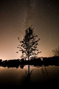 The night sky with a airplane trail on right.  Note star reflections in water.  Cottonwood, Arizona.